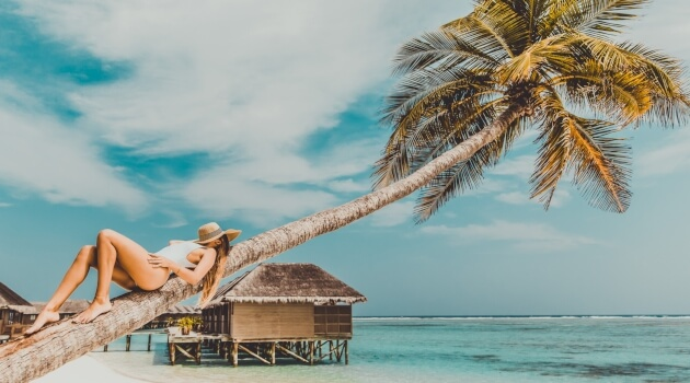 girl-laying-on-a-palm-tree-with-cabin-in-background-051519