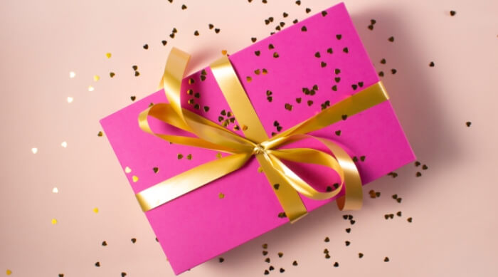 pink wrapped present with a gold bow