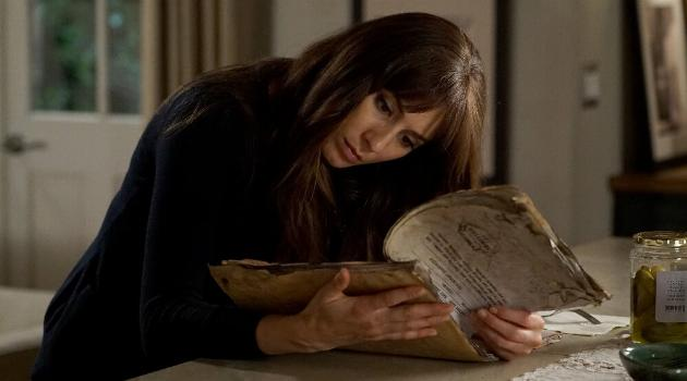 Spencer looking at some old documents in a scene from Pretty Little Liars