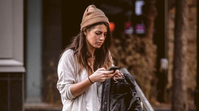 Unsplash: Woman using cell phone in the street social media