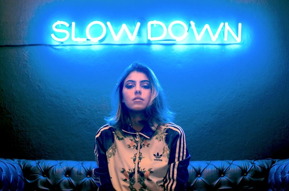 unsplash-daniel-monteiro-woman-in-front-of-slow-down-neon-sign-052919