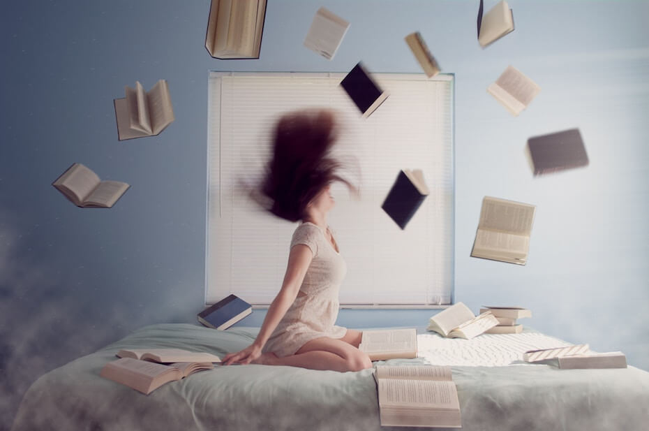 unsplash-lacie-slezak-woman-on-bed-with-books-flying-in-air-052919