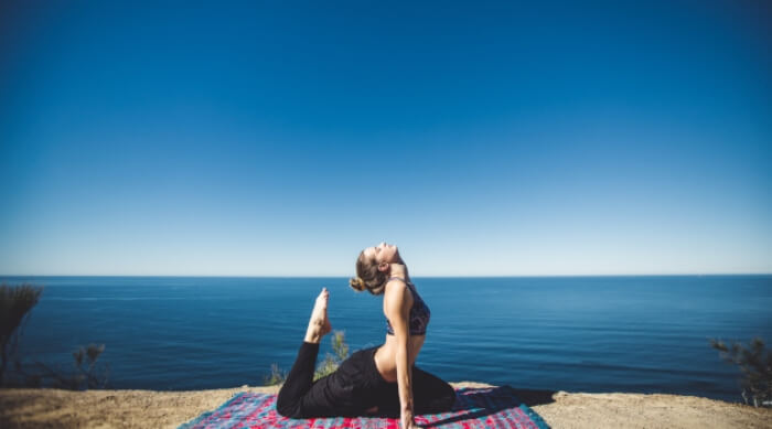 woman doing yoga pose in front of water