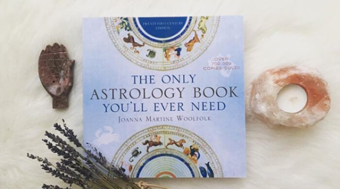 The Only Astrology Book You'll Ever Need on a white fuzzy blanket next to a rose quartz candle and lavender