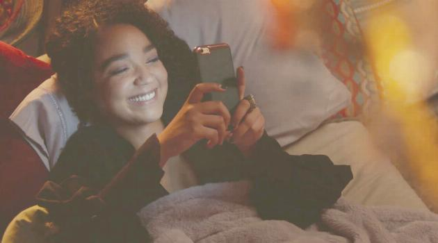 Kat smiling while looking at her phone on The Bold Type