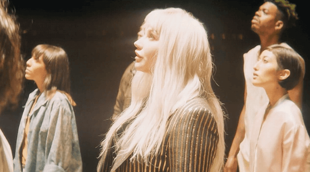 "Kesha staring up at a white light in her music video for ""Hymn"""