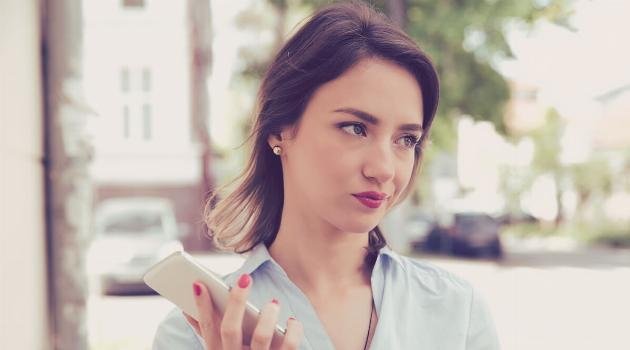 Shutterstock: Woman holding a phone and looking annoyed