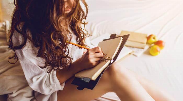 Shutterstock: Woman writing in diary