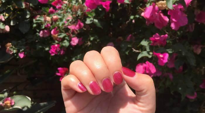 Del Sol: Liquid Sunshine nail polish in sunlight against flowers