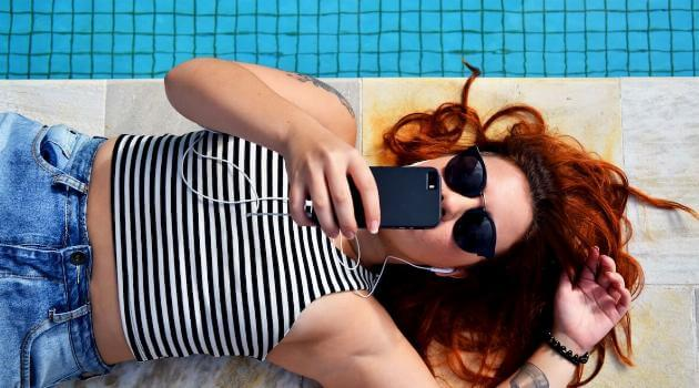 Unsplash: Woman lounging next to pool on her phone