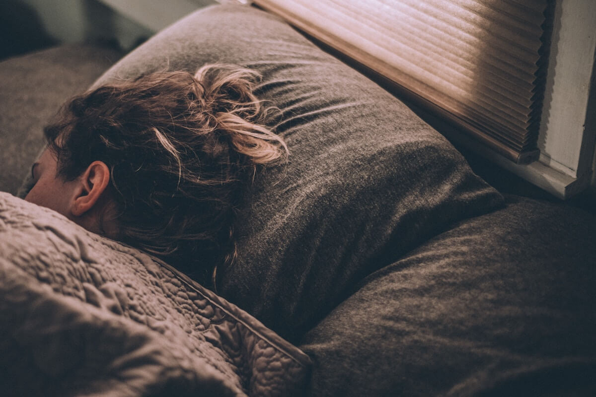 Unsplash: Woman sleeping/dreaming in a comfy bed