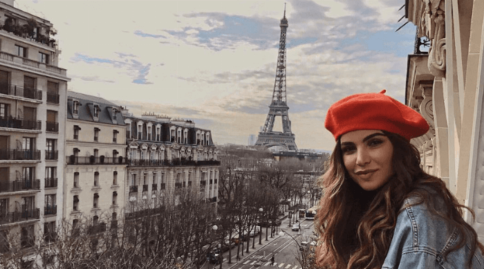 negin in paris wearing a red beret in front of eiffel tower