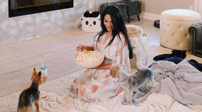 Instagram: Woman in dress holding bowl of popcorn with two dogs