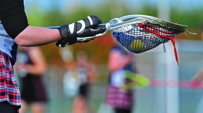 Shutterstock: Girl playing lacrosse with the ball