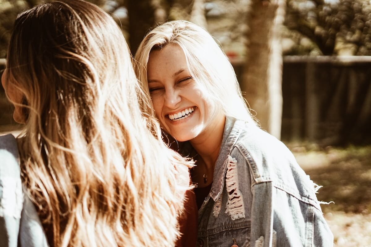 Unsplash: Woman smiling and laughing toward friend
