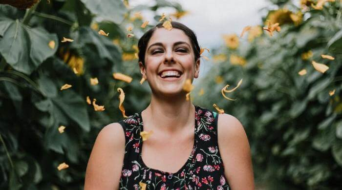 Unsplash: Woman in field smiling with raining yellow petals