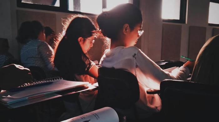 Unsplash: Girls sitting in classroom writing things down