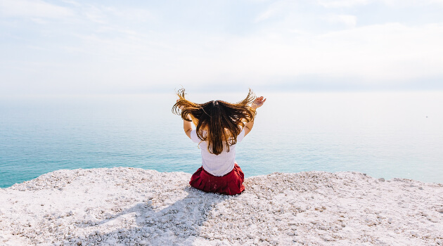 Girl sitting on ledge with her hair blowing behind her