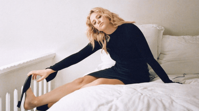 Lili Reinhart sitting on a bed grabbing her foot