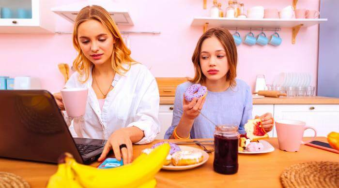 Shutterstock: Older sister working on computer while younger sister eats a donut