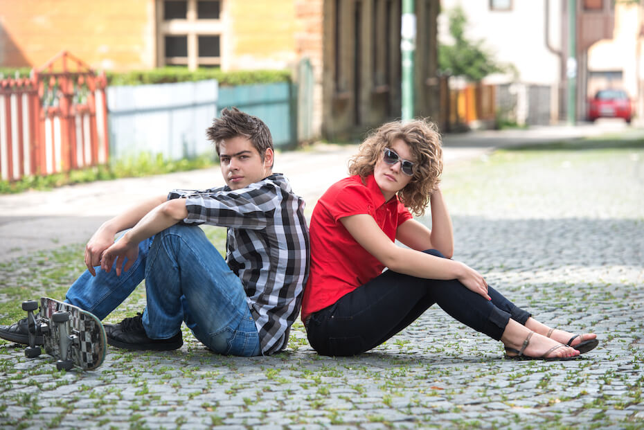 Shutterstock - Teen boy and girl sitting back to back on road