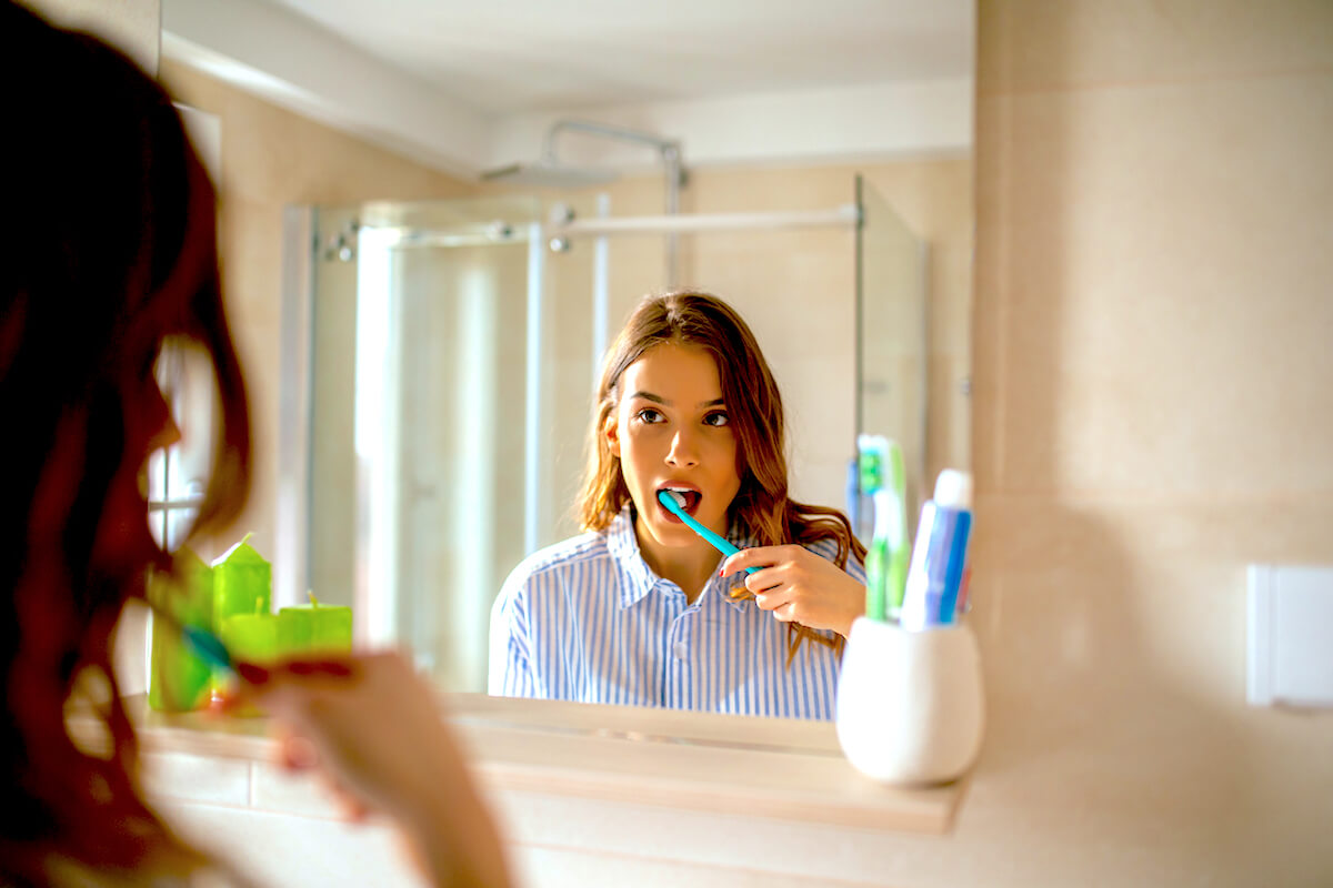 Shutterstock: Woman brushing her teeth in the mirror