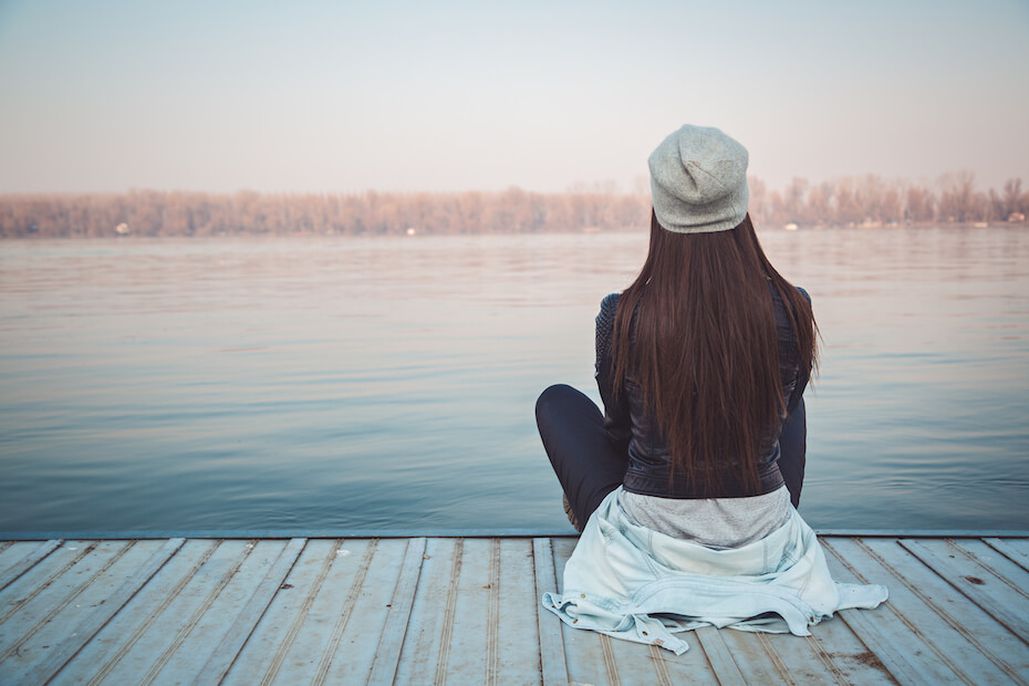 Shutterstock: Woman sitting on a dock overlooking a lake