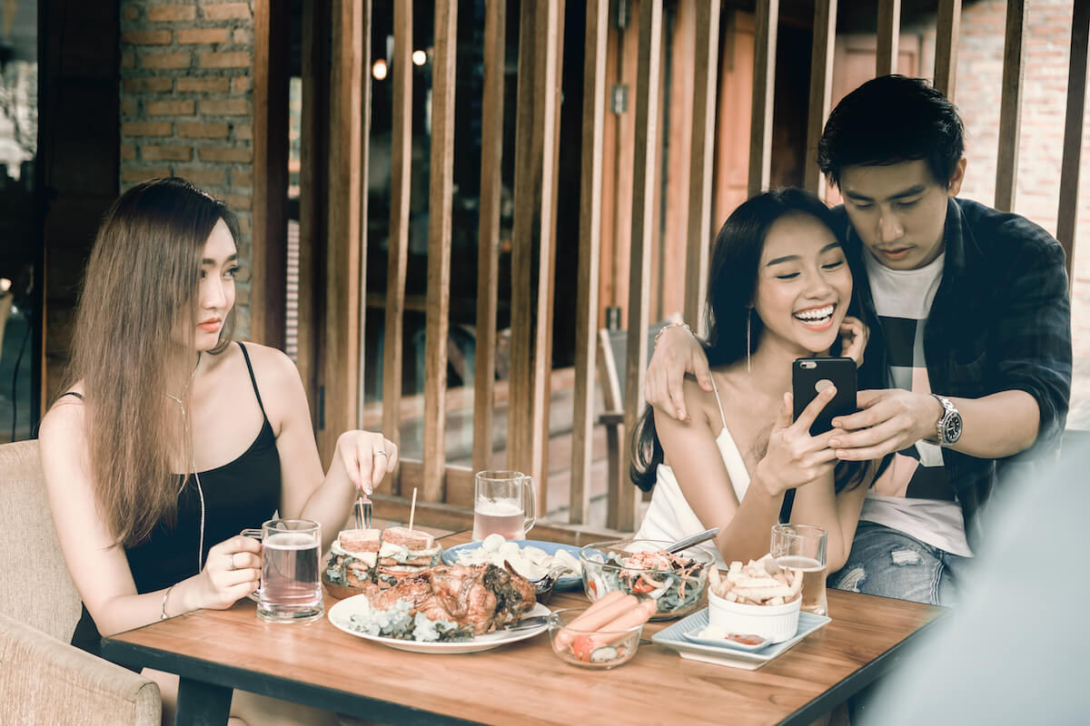 Shutterstock: Woman feels like sad third wheel as friends are laughing together over meal