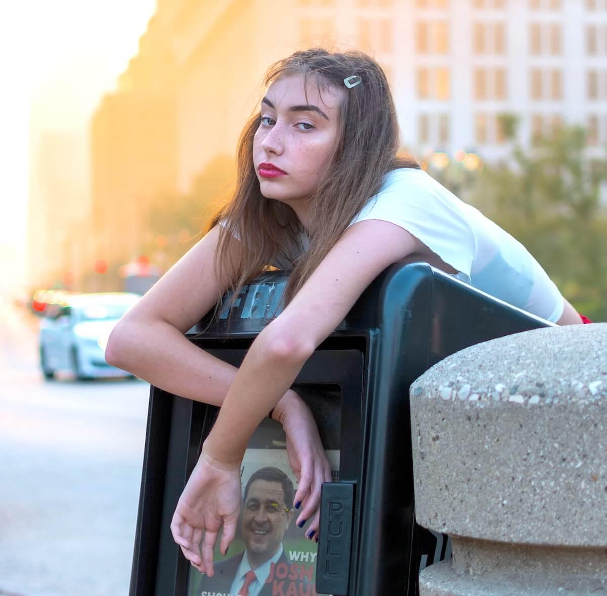Unsplash: Bored girl leaning over newspaper dispensing box