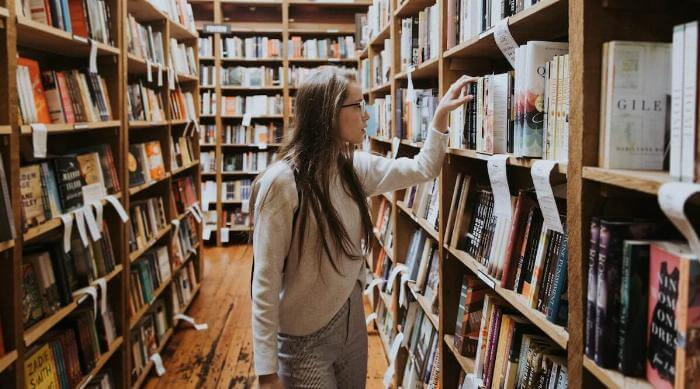 Unsplash: Woman with glasses being curious and exploring book store library