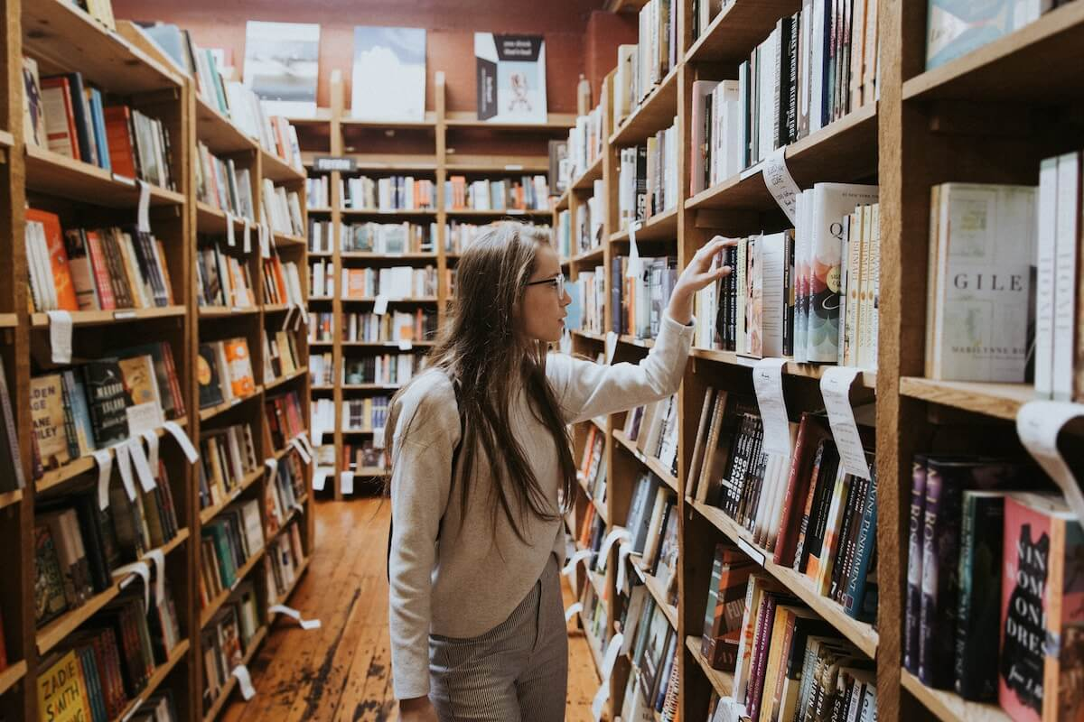 unsplash-becca-tapert-woman-in-glasses-explores-library