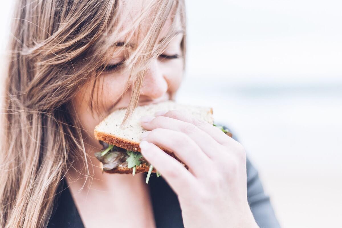 Unsplash: Woman biting into sandwich