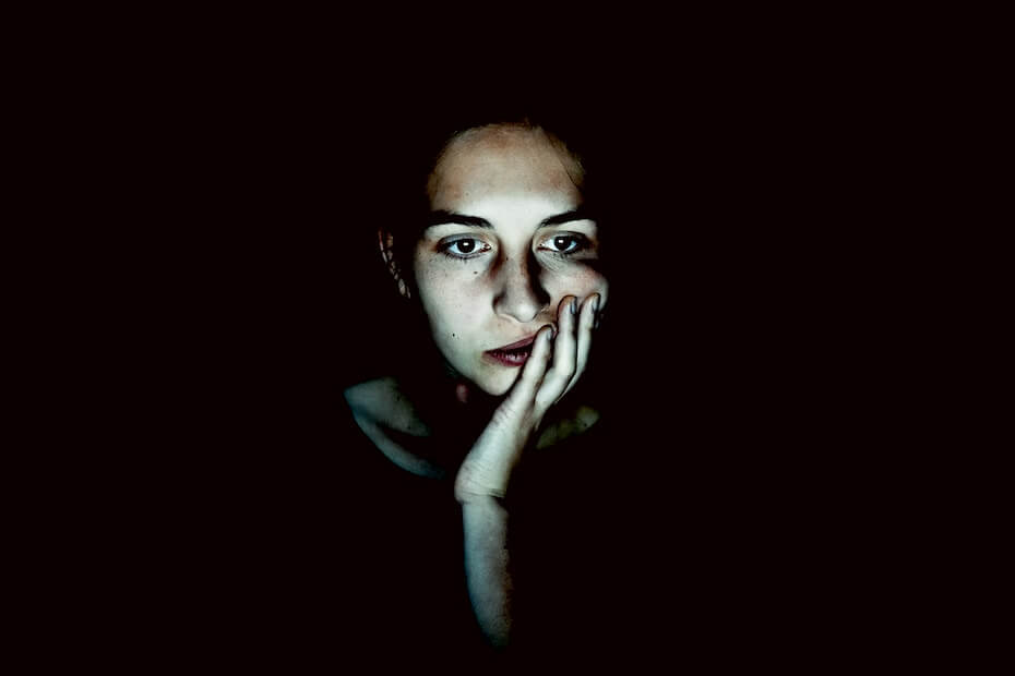 Unsplash: Woman looking worried on black screen