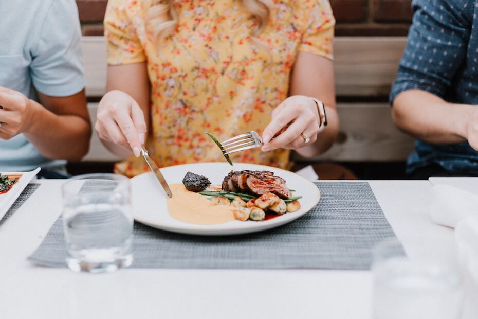 Unsplash: Woman cutting food on her dinner plate