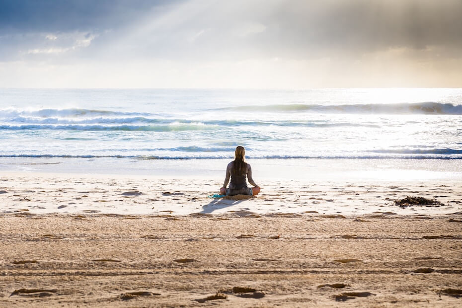 Unsplash: Woman meditating on the beach