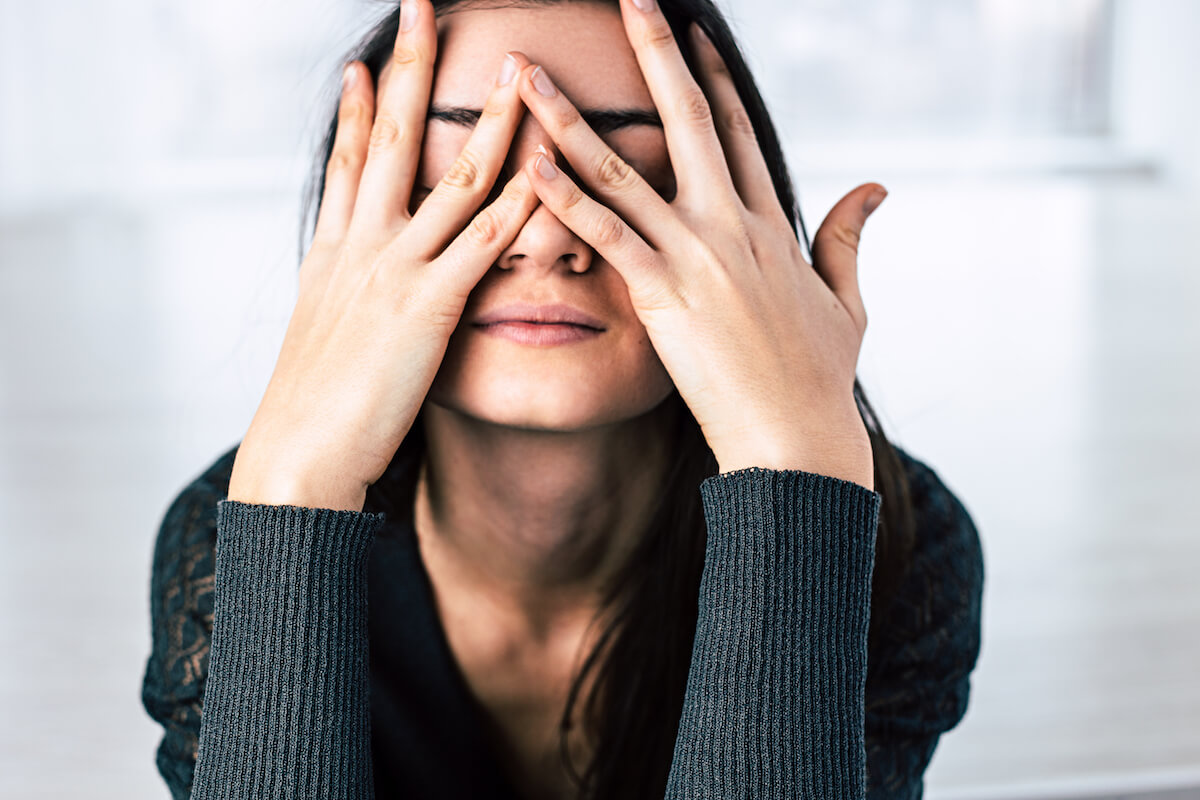 Shutterstock: Stressed woman with hands over her face