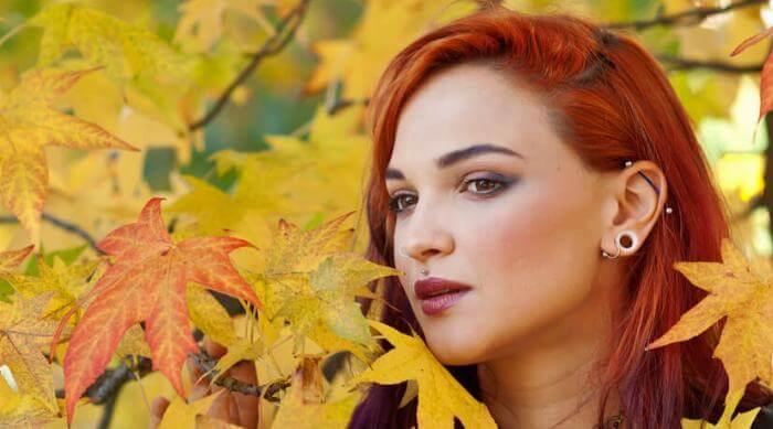 Shutterstock: Woman in fall leaves with ear piercings industrial