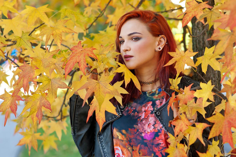 shutterstock-woman-in-fall-leaves-with-ear-piercings