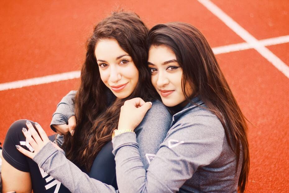 Unsplash: Two friends hugging on track