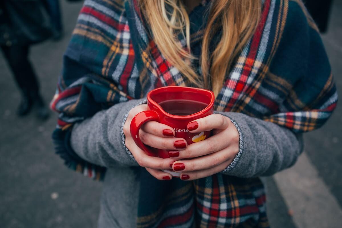 Unsplash: Woman clutching heart mug with tea or coffee