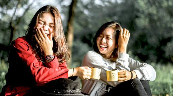 Unsplash: Two girls laughing and smiling in the forest holding mugs