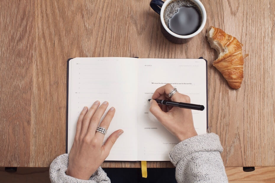 Unsplash: Woman writing to-do list in book with coffee and croissant