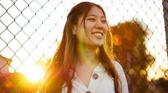 Unsplash: Woman smiling in front of fence at sunset
