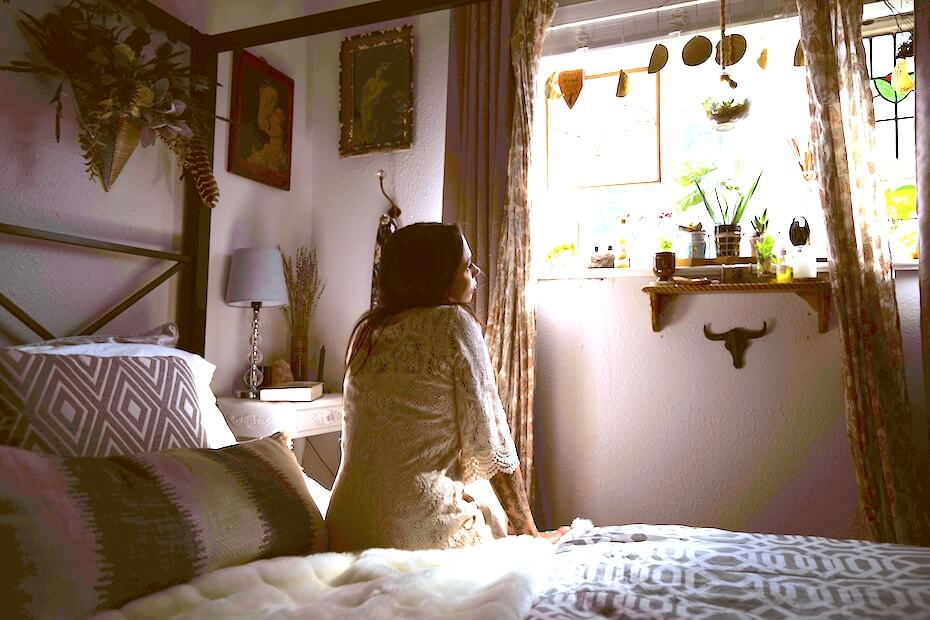 Unsplash: Girl in bedroom looking out window with plants