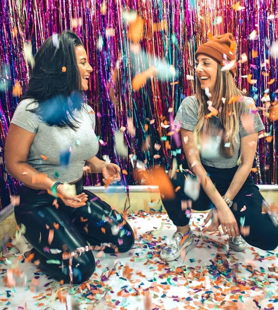 Unsplash: Two women laughing and smiling in room with falling confetti celebration