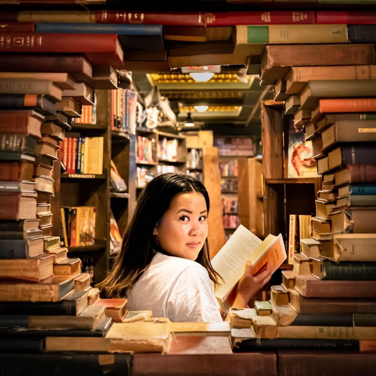 unsplash-francisco-delgado-woman-looking-back-through-stack-of-books