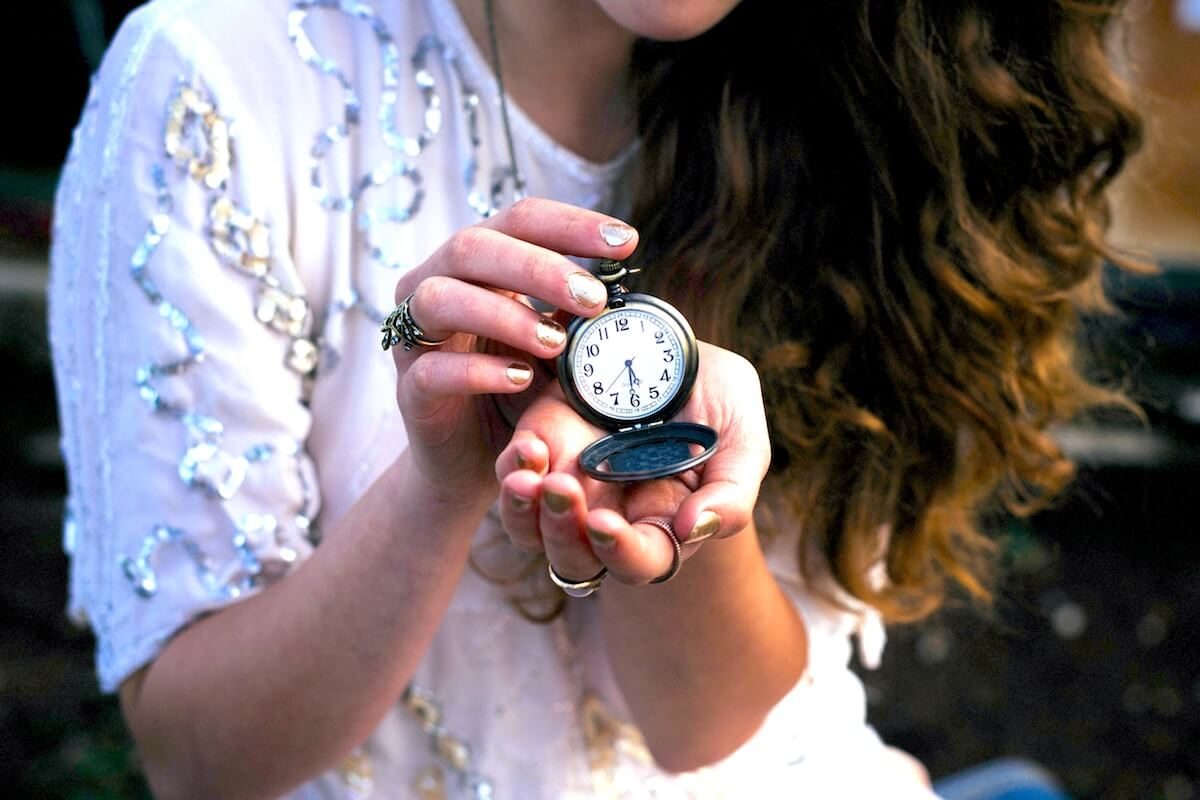 Unsplash: Woman with long hair holding up a pocket watch