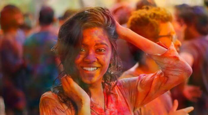 Unsplash: Woman covered in color run pigment and smiling