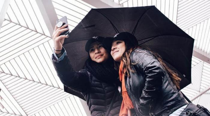 Unsplash: Women taking selfie under an umbrella