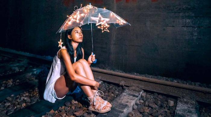 Unsplash: Woman sitting on train tracks alone under a christmas light umbrella